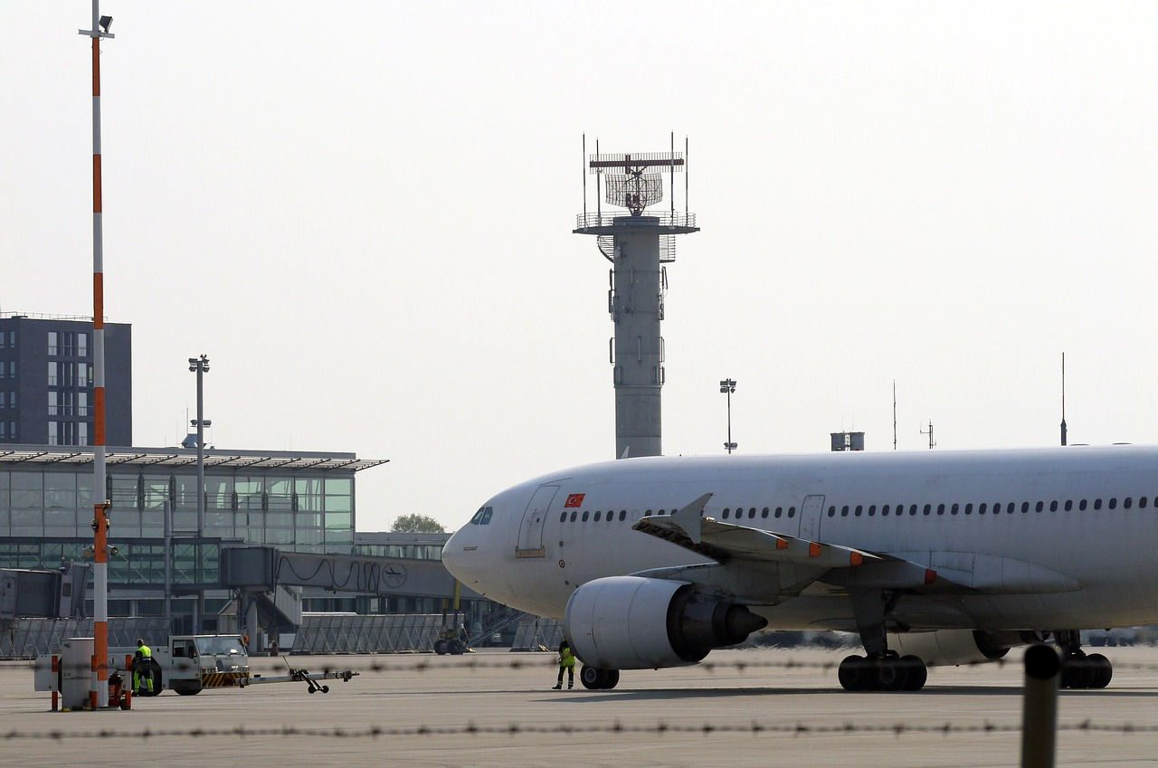 An airliner at an airport with radar tower in the background
